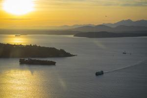 USA, Washington State, Seattle. A Washington State ferry crosses Puget Sound at sunset. by Merrill Images