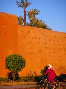 Veiled Woman Bicycling Below Red City Walls, Marrakech, Morocco by Merrill Images