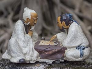 Vietnam, Hanoi. Temple of Literature, painted ceramics of 2 men playing traditional game. by Merrill Images