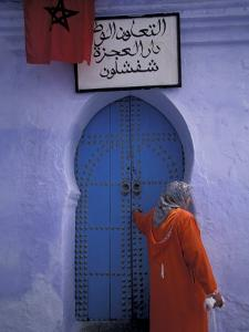 Woman Exits thru Moorish-Style Blue Door, Morocco by Merrill Images
