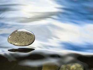 Skipping Stone Just About to Hit the Water's Surface by Michael Durham/Minden Pictures