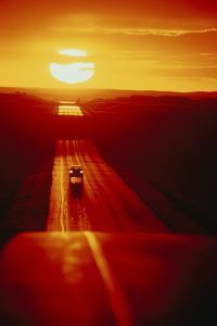 A Car Drives Down a Remote Road at Sunset by Michael Forsberg