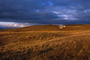 A Solitary Windmill Stands in a Remote Prairie Landscape by Michael Forsberg