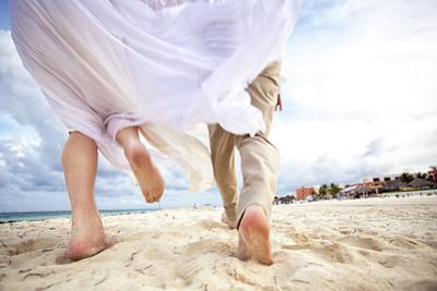 Newlyweds Run Down the Beach on the Riviera Maya in Mexico by Michael Lewis
