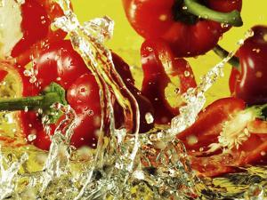 Peppers Falling into Water Against Yellow Background by Michael Meisen