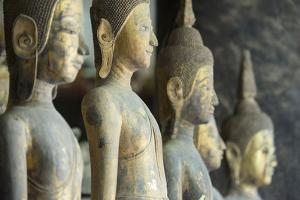 A Row of Standing Buddha Images at Wat Visoun, Commonly known as That Makmo by Michael Melford