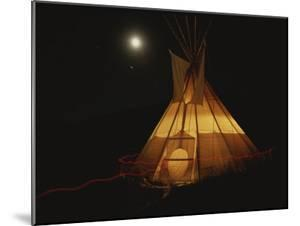 A Tepee is Illuminated against the Night Sky by Michael Melford