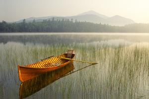 An Adirondack Guide Boat in a Calm Lake with Whiteface Mountain in the Background by Michael Melford