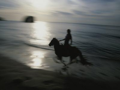 Horseback Rider Silhouetted on Beach, Costa Rica by Michael Melford