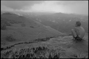 Michael Fay crouches on a mountaintop after nine months in the jungle by Michael Nichols