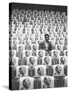Comedian Bill Cosby Sitting in Empty Auditorium Filled with Copies of His Likeness on Each Seat by Michael Rougier