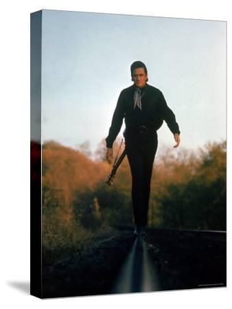 Country Music Star Johnny Cash Walking Along Line of Railway Track with His Guitar
