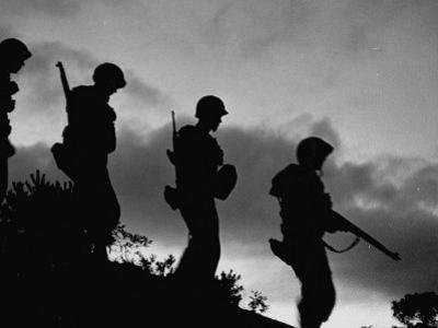 Four Soldiers with Helmets and Rifles Moving on Crest of Ridge, on Patrol at Night
