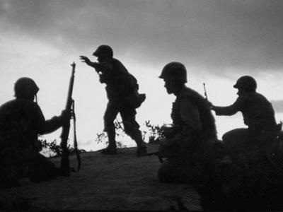 Four Soldiers with Helmets and Rifles Moving on Crest of Ridge, Patroling at Night