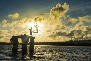 Backlit local boys jumping into the water of the lagoon of Wallis from a platform, Wallis and Futun by Michael Runkel
