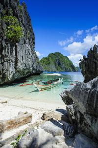 Outrigger Boat on a Little White Beach and Crystal Clear Water in the Bacuit Archipelago by Michael Runkel