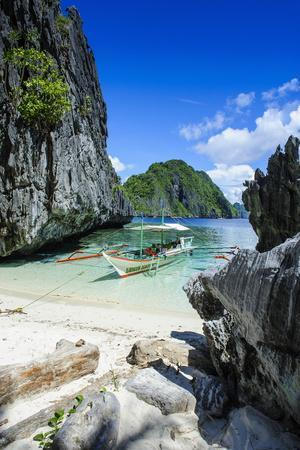 Outrigger Boat on a Little White Beach and Crystal Clear Water in the Bacuit Archipelago
