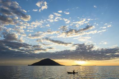 Silhouette of a Man in a Little Fishing Boat at Sunset, Cape Malcear, Lake Malawi, Malawi, Africa by Michael Runkel