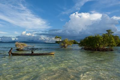 Young Boys Fishing in the Marovo Lagoon before Dramatic Clouds, Solomon Islands, South Pacific by Michael Runkel