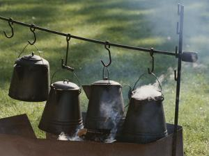 Four Metal Coffee Pots Steaming over an Outdoor Grill by Michael S^ Lewis