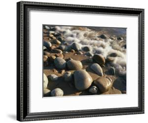 Water Washes up on Smooth Stones Lining a Beach by Michael S. Lewis