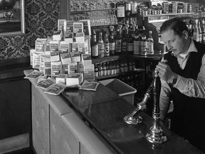 A Pub Landlord with a Display of the Batchelors 5 Day Catering Pack on His Bar, 1968 by Michael Walters