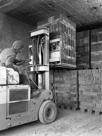 A Yardsman Stacking Pallets of Bricks, Whitwick Brickworks, Coalville, Leicestershire, 1963 by Michael Walters