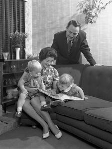 Family Group Looking at a Brochure, Doncaster, South Yorkshire, 1963 by Michael Walters