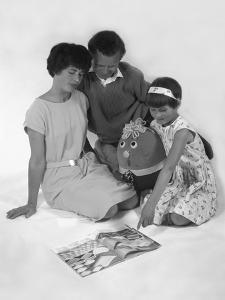 Family Group Looking at a Magazine, 1963 by Michael Walters