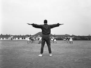 Games Master Taking a Gym Class, Airedale School, Castleford, West Yorkshire, 1962 by Michael Walters
