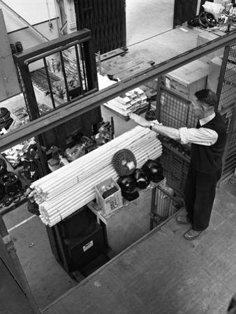 Warehouseman Loading a Fork Lift Truck in the Stores, Bestwood Colliery, Nottinghamshire, 1962 by Michael Walters