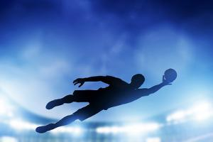 Football, Soccer Match. A Goalkeeper Jumping to Defend, save the Ball from Goal. Lights on the Stad by Michal Bednarek