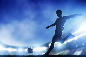 Football, Soccer Match. A Player Shooting on Goal. Lights on the Stadium at Night. by Michal Bednarek