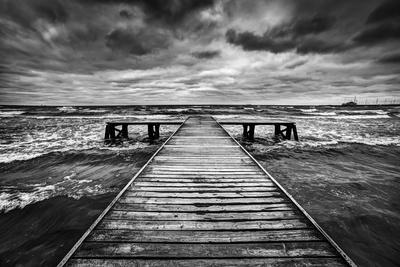 Old Wooden Jetty, Pier, during Storm on the Sea. Dramatic Sky with Dark, Heavy Clouds. Black and Wh