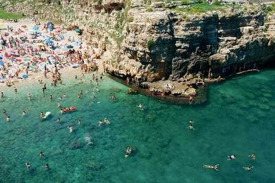 Italia, Apulia, Polignano a Mare. Crowded beach on a weekend. green.