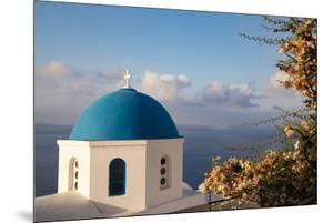 Blue domed Greek Orthodox church with bougainvillea flowers in Oia, Santorini, Greece. by Michele Niles