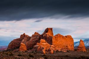 Storm Clouds Passing Above A Sandstone Rock Formation Near The Windows Section. Arches NP, Utah by Mike Cavaroc