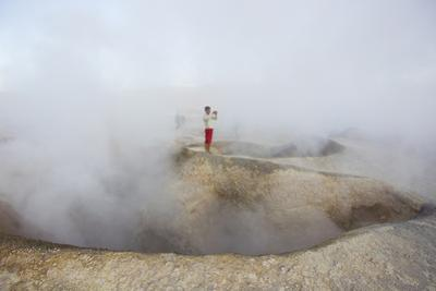 A Man Between Two Craters That Contain Boiling Mud and Steam by Mike Theiss