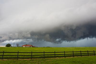 A Supercell Thunderstorm Darkens the Sky over a Ranch and Fields by Mike Theiss