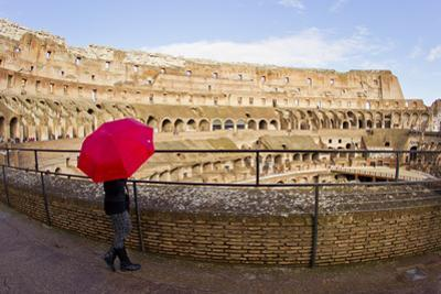 A Woman with a Red Umbrella Inside the Ancient Roman Colosseum