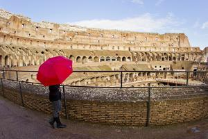 A Woman with a Red Umbrella Inside the Ancient Roman Colosseum by Mike Theiss