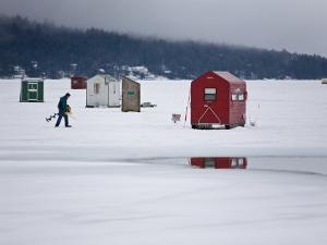 Ice Fisherman with a Drill Walking Among Fishing Shacks on a Frozen Lake by Mike Theiss