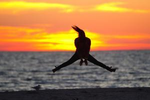 Silhouette of a Woman Jumping in Front of a Colorful Beach Sunset by Mike Theiss