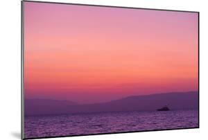 Sunset Turns the Sky Pink and Purple as a Lone Boat Floats Offshore by Mike Theiss