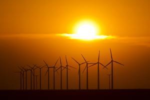 The Sun Sets Behind a Row of Spinning Windmills or Wind Turbines by Mike Theiss