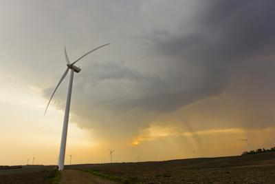 Windmills or Turbines That Produce Kinetic Energy Lined Up on Farms by Mike Theiss