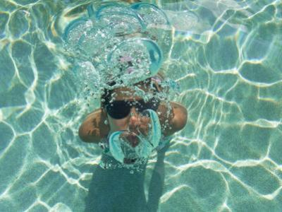 Woman Blowing Bubbles under the Water as She Comes Up for Air by Mike Theiss