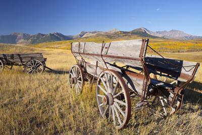 Old Horse-Drawn Wagons with the Rocky Mountains in the Background, Alberta, Canada by Miles Ertman