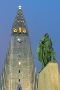 The Hallgrims Church with a statue of Leif Erikson in the foreground lit up at night, Reykjavik, Ic by Miles Ertman
