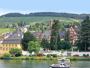A Yacht Sails by the Town of Traben-Trarbach, Germany by Miva Stock